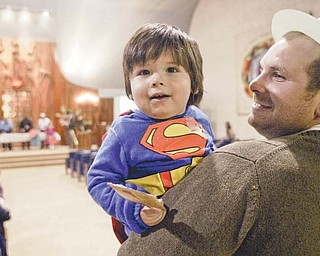 "One-year-old Eli Clayman-Smith, held by his father, Matt Smith, is in the spirit of a ""super"" Purim on Wednesday night at Temple El Emeth in Liberty. The holiday, complete with costumes and funny hats, was celebrated with a reading from the Book of Esther on how the Jews in Persia defeated the evil Haman. Participants sounded ""groggers"" to boo the name of Haman when it was mentioned."