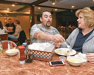 Dustin Shamp tries to sample a bite of fish from his fiancée, DeAnna Hardwick, of Poland at the weekly fish fry at the Youngstown Maennerchor on Mahoning Avenue. The couple has been coming to the dinners for years.
