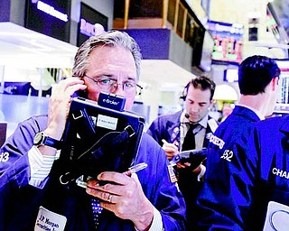 Trader Thomas Kay, left, works on the floor of the New York Stock Exchange on Friday.