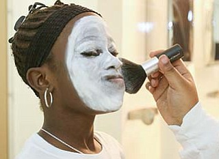 Cierra Gordon, 10, of Austintown holds her breath as white powder is applied to her face to look the part of a mime.
