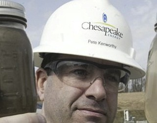 Pete Kenworthy, manager of media relations for Chesapeake Energy Corp., holds two jars of water. The first, on the left, contains produced water from the fracking process. The jar on the right contains treated water that will be reused at another well.