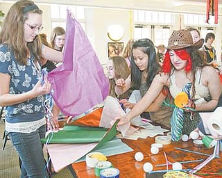 "Kayla Theisler, 16, of Lowellville picks up tissue paper during the first ""The Hunger Games"" challenge at the Poland Branch library. Kayla and the rest of the designers had to choose random materials and design an outfit based on the 12 districts from the book."