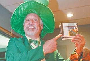 Chuck Simon of Salem, an actor originally from Youngstown, dresses up and shows off CDs for purchase from the band Brady's Leap. The group played a set Thursday at the Kravitz Deli St. Patrick's Kick Off Celebration in