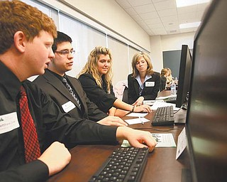 "Boardman White Inc. ""executives"" Matthew Zook, left, Andrew Ripple and Betsy Bresnahan, seniors at Boardman High School, with their coach Melissa Payne, try to market their product in a diffi cult economy. They were among high-school seniors competing Thursday in the Junior Achievement of the Mahoning Valley's third annual Titan Business Challenge at Williamson College of Business Administration, Youngstown State University."