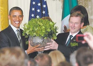 President Barack Obama, left, holds up a bowl of shamrocks that was presented to him by Irish Prime Minister Enda Kenny, right, during a St. Patrick's Day reception in the East Room of the White House in Washington on Tuesday.