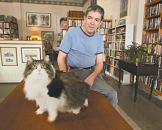 A familiar fixture at Dorian Books, a used bookstore on Youngstown's North Side, is Ernest Hemingway, a 28-pound, 8-year-old cat, adopted from a Columbus animal shelter. Ernie, named after the renowned novelist, is shown with his owner, Jack Peterson, bookstore co-owner.