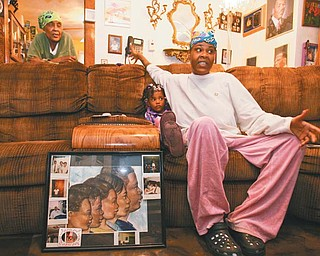 Maggie Williams, far left, and her daughter, Reice Williams, spoke to The Vindicator near a drawing of the five children of Julius Williams, framed and surrounded byimages of Julius and his family. Julius was killed by his wife, Monique, in 2008. Mylah Arington, 3, stayed close to her mother as the child listened to stories about