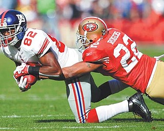 San Francisco 49ers cornerback Carlos Rogers (22) will no longer be chasing down New York Giants wide receiver and Warren Harding grad Mario Manningham (82). The two officially became teammates Thursday when Manningham inked a two-year deal with the Niners.
