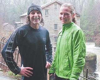 Terry McCluskey poses with friend and fellow runner Sarah Flament of Poland near Lanterman's Mill at Mill Creek Park, which he says is his favorite place to train. McCluskey, 62, a native of Farrell, Pa., was named the Masters Division male runner of the year by the Road Runners Club of America.
