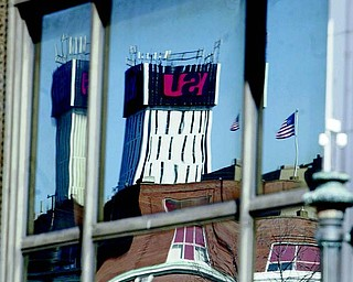 The YSU logo is reflected in Stambaugh Building window.