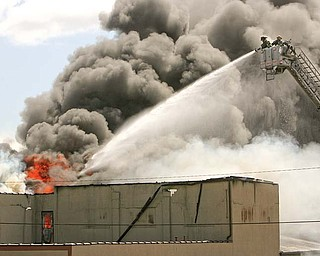 Youngstown firefighters spray water to control a blaze at an industrial building on the city's lower North Side. The department was busy Monday with two simultaneous fires, this fire at 837 Madison Ave. and a smaller fire at a house at 23 Hilton Ave.