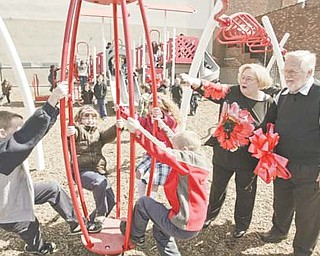 Virgina Rice Smith, second from right, and her husband, Frank Smith, watch as St. Rose School students try out the new playground Monday. The school named the playground for the 37-year teacher after her husband made the highest bid for naming rights during the project's fundraising auction.