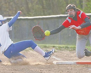 Poland's Amanda Kabetso (7) slides safely back to first base on a pick-off attempt by Girard during their game Tuesday in Girard. Indians first baseman Bryanna Jay reaches for the ball on the play.