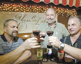 Partners Dr. Mark Elisco, left, John A. Jurko and Mark Masters sample a variety of Yankee Lake wine.