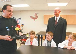 Dr. James Chengelis shows a solar-system model to Stadium Drive Elementary students Sami DeFabio, a kindergarten student; Sean Guerriero, also kindergarten; and Gia Triveri, a first-grader. Stadium Drive Principal Jim Goske, center, said the school is grateful for Chengelis' donation of a school science lab.