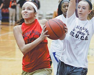Lowellville's Ashley Moore, playing for the Red Team, drives to the hoop after getting past the White Team's Rachel Ellis of Newton Falls during the Al Beach Classic on Wednesday at Boardman High School. Red defeated White, 54-49, in overtime, with Moore named the game's Most Valuable Player.