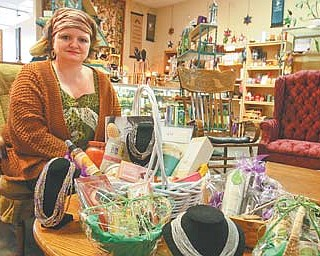 Michele Stratton-Barratt, owner of The Flaming Ice Cube, a vegan café and shop in the Creekside Plaza, Boardman, shows off some items that will be available at a charity auction Saturday to benefit the Rescue Mission of the Mahoning Valley.