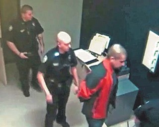 In this image taken from video at the Sanford, Fla., Police Department, George Zimmerman, in red jacket, is escorted into the Sanford police station in handcuff s Feb. 26, the night he fatally shot Trayvon Martin.