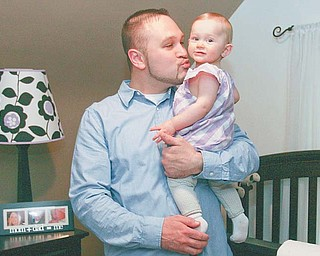 Kenley Schiraldi, who will be 1 year old this month, is a miracle baby conceived with the help of a new technique for sperm preservation. Cuddling her is dad Jason. The family, including mom Jennifer, lives in Campbell.