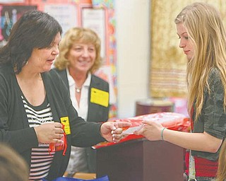 Orly Menasherov, a middle school teacher in Akka, Israel, gives a gift to Samantha Barker, an eighth-grader at W.S. Guy Middle School in Liberty, for winning a game of naming Israeli flowers. Looking on is Ednar Goldsmith, an Israeli school principal.