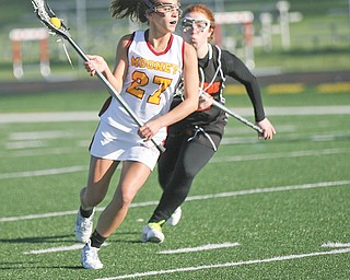 Cardinal Mooney's Makenna Ozenghar, pursued by Orange defender Arianna Cerqueira, looks to pass during the first half of a lacrosse game Wednesday at Mooney High School. The Cardinals dominated the Lions, 16-0.