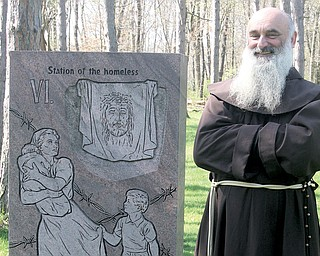 The Rev. Vit Fiala, a Franciscan friar at Shrine of Our Lady, Comforter of the Afflicted, stands beside an Iron Curtain Station of the Cross on shrine grounds. The sixth station is Veronica wiping the face of Jesus,  exemplified by a face on cloth; the Iron Curtain version depicts homelessness.