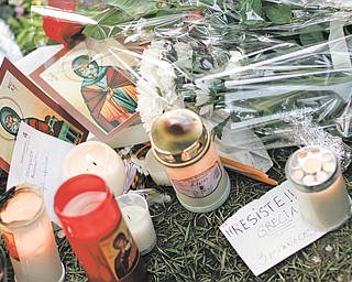 A note in Spanish sits among candles, flowers and cards that people left at the site where a 77-year-old man shot himself in the head Wednesday on Syntagma square in Athens, Greece. Police clashed with demonstrators for a second day Thursday at the site.
