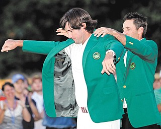 Charl Schwartzel, right, of South Africa, helps Bubba Watson put on the green jacket after winning the Masters golf tournament after a sudden-death playoff on the 10th hole Sunday in Augusta, Ga.