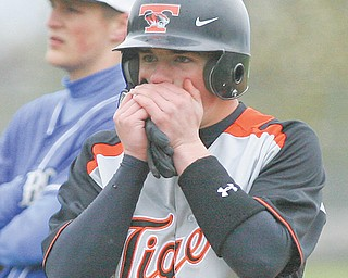 Springfield's Hunter Snyder takes a second to warm up his hands after reaching first base during the bottom of the second inning at Tuesday's baseball game against Lisbon in New Middletown. The Tigers were leading 12-2 when the game was suspended in the bottom of the inning due to inclement weather. The teams will finish today before their regularly-scheduled clash at Lisbon.