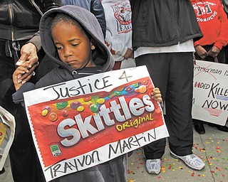 """Steven Jonhson, 3, holds an enlarged banner of Skittles candy as he joins Los Angeles community members at a """"Justice for Trayvon Martin hoodie rally"""" to protest the death of Trayvon Martin, an unarmed black teenager who was shot and killed by neighborhood watch captain George Zimmerman."""