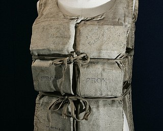 A Titanic life-preserver, belong to a survivor, which is being auctioned in a Christie's Maritime sale, London, Wednesday, May 16, 2007. The century-old canvas jacket, lined with buoyant cork, belonged to Mabel Francatelli, one of 12 passengers to escape from the RMS Titanic in a lifeboat built to fit 40, the London-based auction house said. Her vest _ carrying her faded signature and those of seven other survivors _ was offered for sale along with a letter she wrote describing what happened that night. The lot was expected to sell for at least 50,000 pounds (US$100,000; 70,000), Christie's said.((AP Photo/Sang Tan)