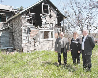 Austintown Township Trustee David Ditzler, left, Fiscal Officer Laurie Wolfe and Zoning Inspector Darren Crivelli stand in front of a dilapidated property at 252 Four Mile Run Road, one of six homes on the township's demolition list. But lack of funding is preventing the township from demolishing four of them, including this abandoned house.
