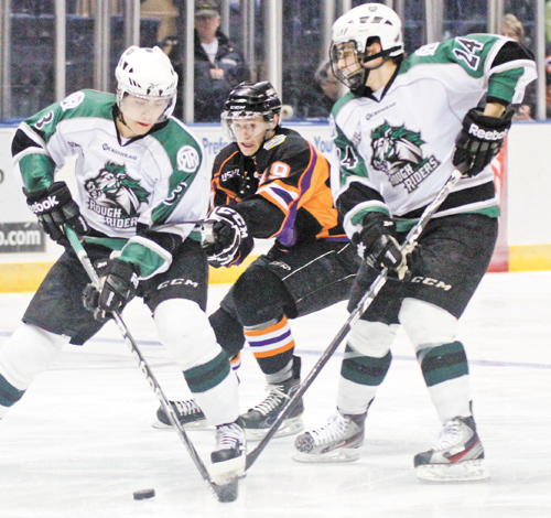 Dylan Margonari of the Youngstown Phantoms, center, keeps his eye on the puck as Cedar Rapids RoughRiders' John Gilmour, left, and Ian Brady try for control during the first period of Monday's playoff game at the Covelli Centre.