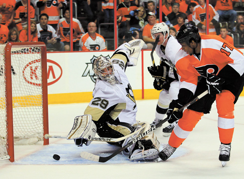 Philadelphia Flyers' Wayne Simmonds, right, puts the puck past the reach of Pittsburgh Penguins goalie Marc-Andre Fleury for a goal during the second period of Game 3 in a first-round NHL Stanley Cup playoff series Sunday in Philadelphia.