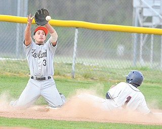 Howland third basemen Tim Schulman (3) goes to his knees to catch a throw as Austintown Fitch's Alex Sierra slides into third base during Tuesday's game.