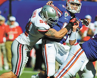 Florida quarterback John Brantley (12) is sacked by Ohio State defensive tackle John Simon (54), a Cardinal Mooney graduate, during the first half of the Gator Bowl in Jacksonville, Fla.