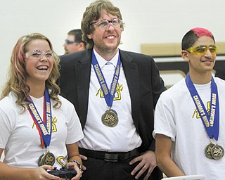 Warren G. Harding High School senior Samantha Arthur, left, controls a student- built robot, while the robotics team coach Keith Rising and senior team member Tyler Nimmagadda look on. The team will compete in a national robotics competition April 25-28 in St. Louis.