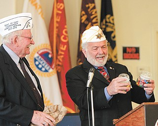 "James Graham, AMVETS Department of Ohio commander, left, gives John ""J.P."" Brown III of Boardman, former state and natonal AMVETS commander, candy as an honorary gift for AMVETS Post 44, 305 Elm St., Struthers, which had a grand opening Wednesday."