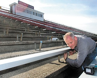 John McCague, of Buckeye Bleacher Repair in Sunbury, Ohio, installs new aluminum bleachers Wednesday morning in a section of Falcon Stadium in Austintown. The bleachers are replacing the last remaining section of original wooden bleachers, which were installed when the stadium was built in 1970.