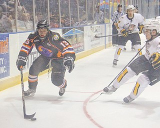 Phantoms' Ryan Lowney (13) tries to keep control of the puck while being defended by the Gamblers' Dakota Mermis during the first period of the second-round USHL playoff game Tuesday at the Covelli Centre in Youngstown.