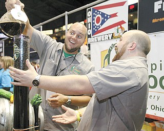 Bottlers Jeff Riggs and Dave Hoopes pour Italian roast coff ee into Hoppin' Frogs signature Silk Porter to distribute at the Big Tap In craft beer festival Saturday at Covelli Centre.