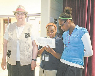 Destiny Gregory, 10, center, and her classmate, Erica Carlisle, 12, read about Mary Leyman, left, a resident of the Goodwill Apartments and their literacy buddy during a book-release event at Taft Elementary School. Taft and Williamson Elementary schools students in the Youngstown Super STARS Afterschool program compiled information during interviews with senior citizens to create a book about the seniors' lives.
