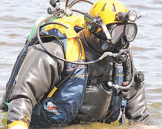 John Mesmer of Struthers slowly walks backward into McKelvey Lake in Youngstown where the Mahoning County sheriff 's dive team trained Sunday in locating evidence at the bottom of a lake.