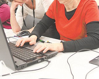 Supervisor and trainer Judy Sluss, left, of the Public Library of Youngstown and Mahoning County helps Theresa Semchee during a class on downloading eBooks.