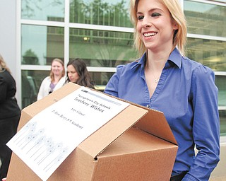 Lindsay Czopur, an employee of Turning Technologies, carries one of the boxes headed to P. Ross Berry Eighth and Ninth Grade Academy.