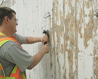 Travis Csuti , 35, of Youngstown, a participant in the day-reporting work program of the Mahoning County Sheriff 's Office, removes paint and staples from the side of a barn at the Canfield Fairgrounds. He was among five day-reporting offenders scraping and painting horse barns there Wednesday.