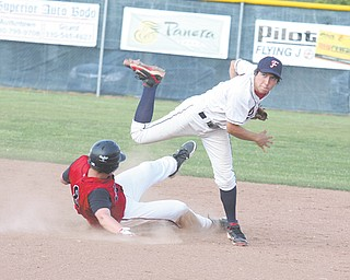 Fitch's Tony Adams (4) follows through as Nick Gigax (8) of Struthers tries to break up the play during an All-American Conference baseball game Wednesday in Austintown. The Falcons edged the Wildcats, 9-8.