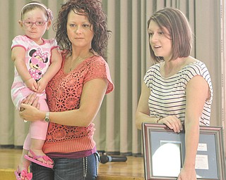 Madison Antal, 5, and her mom, Cristal Antal, both of Lordstown, left, presented an appreciation plaque Thursday to Poland Union Elementary students who raised funds to support Madison's Make-A-Wish project. Make-A-Wish representative Kim Sazima, right, also was on hand to thank the students.