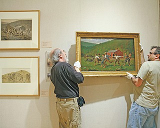 """Butler Institute of American Art employees Ray Johnson, left, and Wayne Gruver hang the newly reframed painting """"Snap the Whip"""" in a gallery at the museum Thursday."""