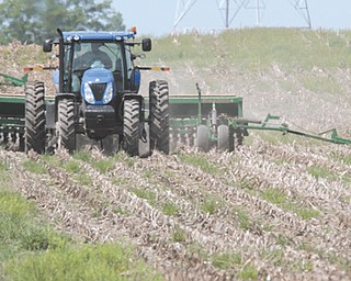 Wayne Greier, owner of Greier Ag Center Inc. near Canfield, works the crops atop his tractor. Despite the late April freeze in much of the state, the Ohio Corn and Wheat Growers Association predicts a record year for corn based on prices and earlier than normal warm weather.